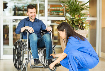 a photo of a caregiver with a man on a wheelchair