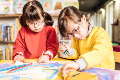 cute appealing sisters having down syndrome feeling involved in coloring pictures