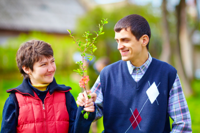 portrait of happy young woman and man with disability together on spring lawn